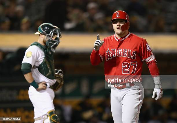 Mike Trout of the Los Angeles Angels reacts as he crosses in front of Jonathan Lucroy of the Oakland Athletics after he hit a home run in the fourth...