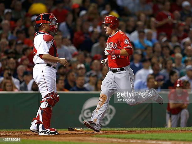 Mike Trout of the Los Angeles Angels scores a run as catcher Christian Vazquez of the Boston Red Sox looks down field in the third inning against the...