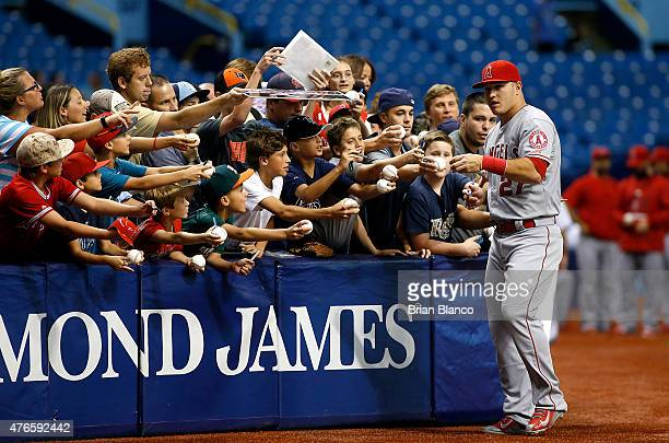 Mike Trout of the Los Angeles Angels signs autographs for fans before the start of a game against the Tampa Bay Rays on June 10 2015 at Tropicana...