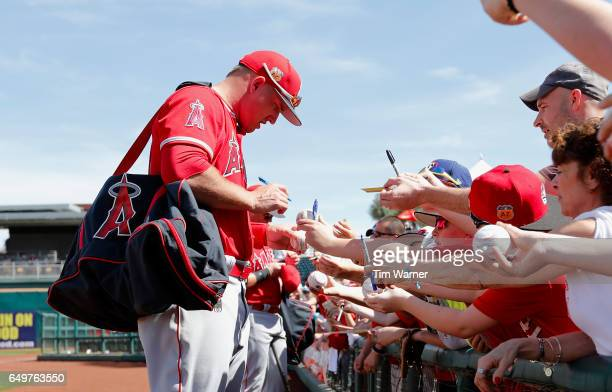 Mike Trout of the Los Angeles Angels signs autographs for fans before the spring training game against the Cincinnati Reds at Goodyear Ballpark on...