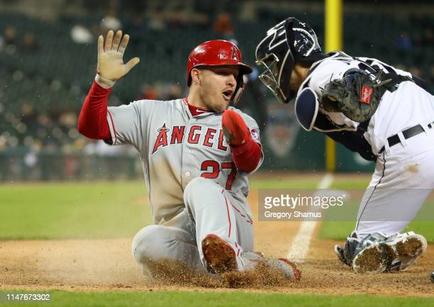 Mike Trout of the Los Angeles Angels slides past the tag of Grayson Greiner of the Detroit Tigers to score in the ninth inning at Comerica Park on...