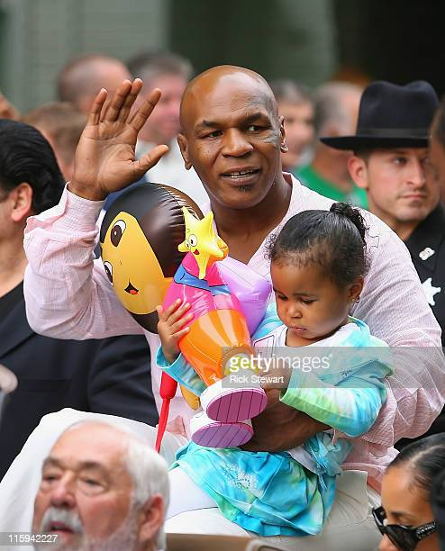 Mike Tyson acknowledges the crowd with his daughter Milan during the Parade of Champions prior to the 2011 International Boxing Hall of Fame...