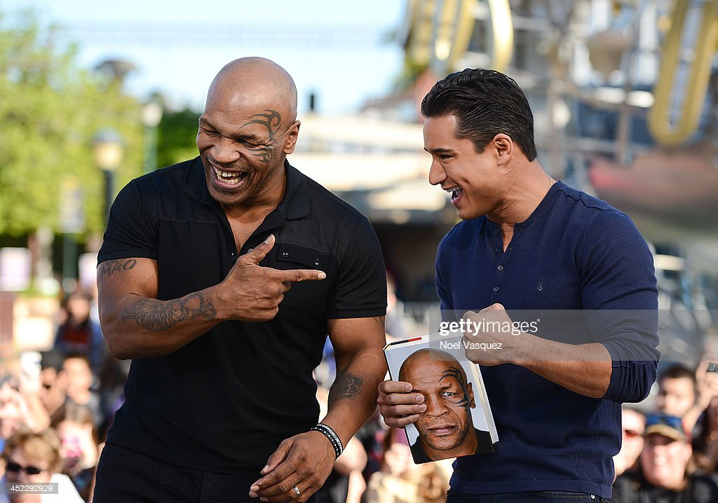 Mike Tyson (L) and Mario Lopez visit 'Extra' at Universal Studios Hollywood on November 27, 2013 in Universal City, California.