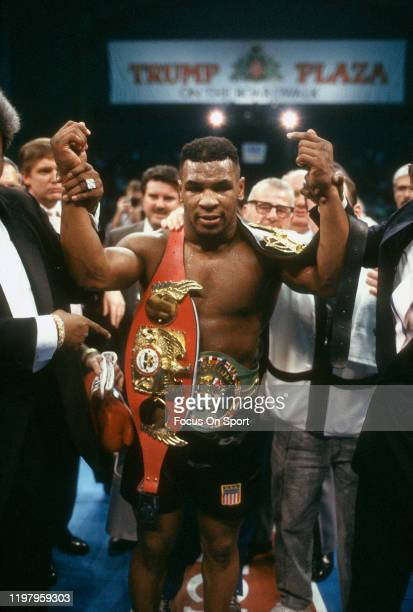 Mike Tyson celebrates wearing all three belts after he defeated Larry Holmes for the WBA, WBC and IBF heavyweight tittles on January 22, 1988 at the...