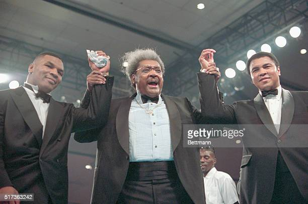 Mike Tyson, Don King, and Mohammed Ali, all clasping hands wearing tuxedos in the boxing ring at the Las Vegas Hilton.
