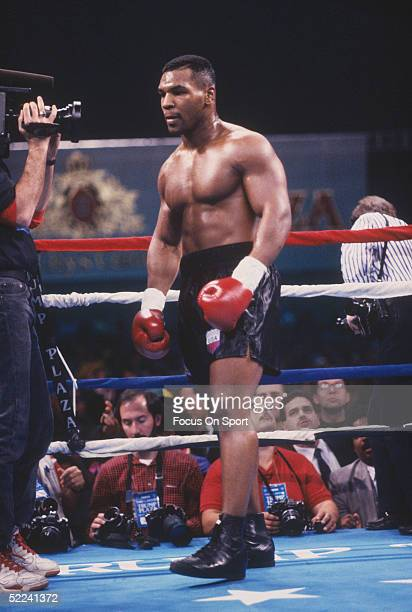 Mike Tyson heads back to his corner as a TV crewman gets close for a shot.