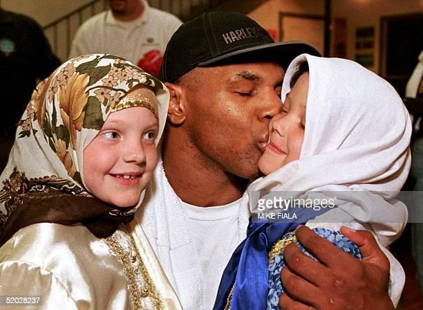 Mike Tyson kisses fiveyearold Fatima Ali as sevenyearold Zaneb Ali lookson after the sisters sung the former heavyweight boxing champion an Islamic...