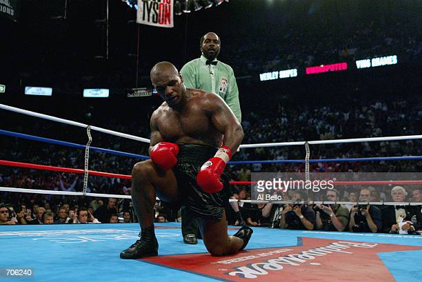 Mike Tyson struggles to his feet after being knocked down by Lennox Lewis during their WBC/IBF heavyweight championship bout on June 8, 2002 at The...