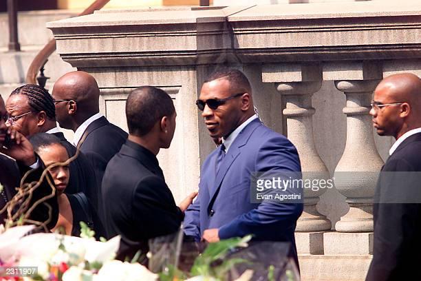 Mike Tyson talks with Usher leaving R B singer Aaliyah's memorial service at St Ignatius Loyola Roman Catholic Church in New York City 8/31/2001...