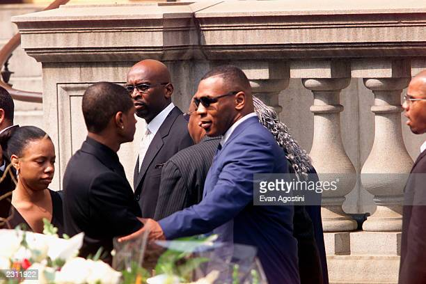 Mike Tyson talks with Usher leaving R B singer Aaliyah's memorial service at St Ignatius Loyola Roman Catholic Church in New York City 8/31/2001...