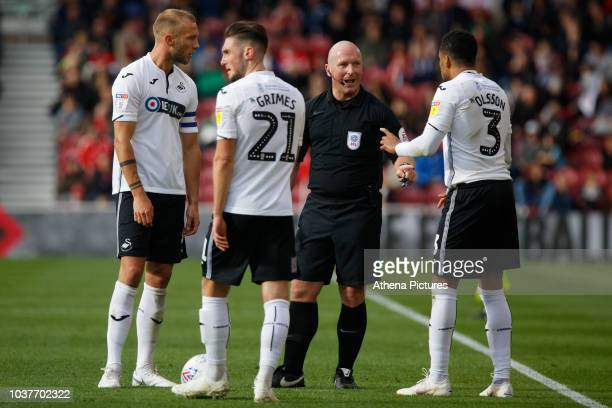 Mike van der Hoorn Matt Grimes and Martin Olsson of Swansea City protest to referee Simon Hooper during the Sky Bet Championship match between...