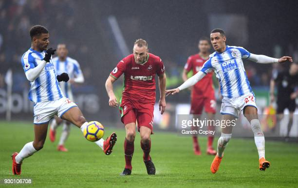 Mike van der Hoorn of Swansea City battles for the ball with Tommy Smith and Tom Ince of Huddersfield Town during the Premier League match between...