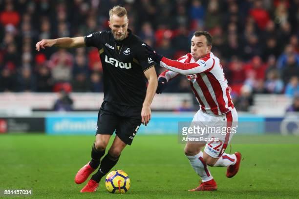 Mike van der Hoorn of Swansea City is challenged by Xherdan Shaqiri of Stoke City during the Premier League match between Stoke City and Swansea City...