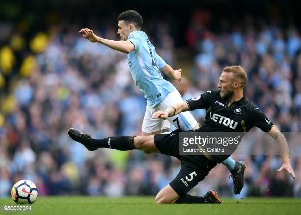 Mike van der Hoorn of Swansea City tackles Phil Foden of Manchester City during the Premier League match between Manchester City and Swansea City at...
