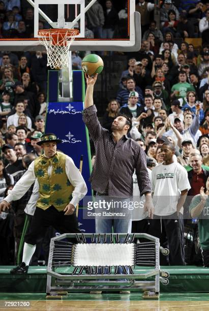 Mike Vrabel of the New England Patriots helps Luck the Boston Celtics mascot do one of his stunts during the game against the Cleveland Cavaliers on...