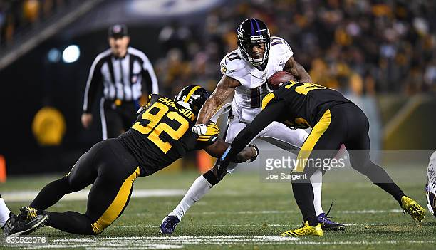 Mike Wallace of the Baltimore Ravens tries to avoid a tackle by James Harrison of the Pittsburgh Steelers in the second half during the game at Heinz...