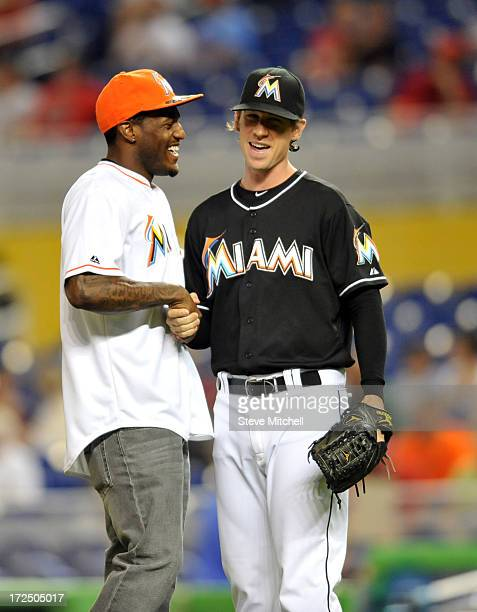 Mike Wallace of the Miami Dolphins greets Kevin Slowey of the Miami Marlins after Wallace throw out the first pitch before a game between the St...