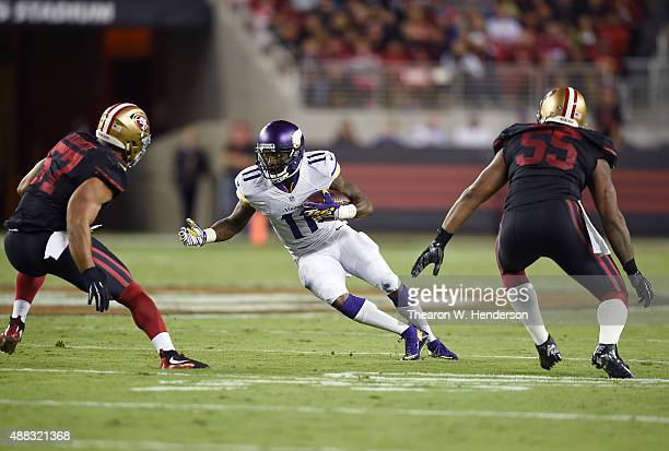 Mike Wallace of the Minnesota Vikings runs with the ball while pursued by Michael Wilhoite and Ahmad Brooks of the San Francisco 49ers during their...
