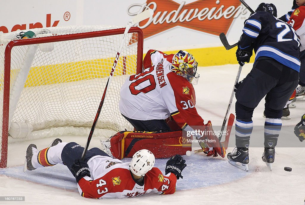 Mike Weaver #43 lies on his back as he tries to help Scott Clemmensen #30 of the Florida Panthers protect the net as Nik Antropov #80 of the Winnipeg Jets tries to find the puck during NHL action on February 5, 2013 at the MTS Centre in Winnipeg, Manitoba, Canada.