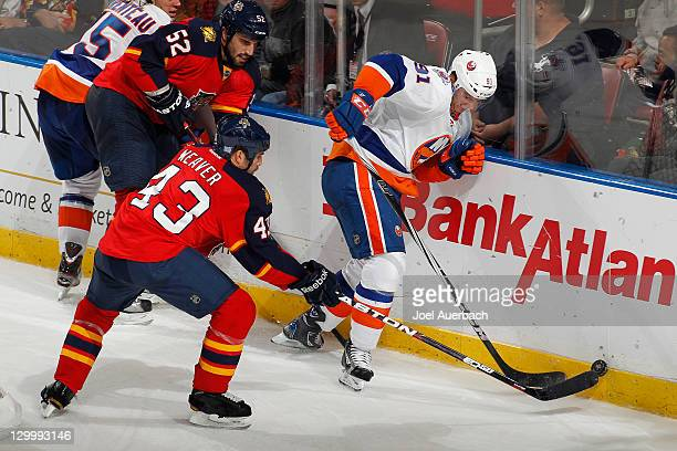 Mike Weaver of the Florida Panthers and John Tavares of the New York Islanders fight for control of the puck on October 22 2011 at the BankAtlantic...