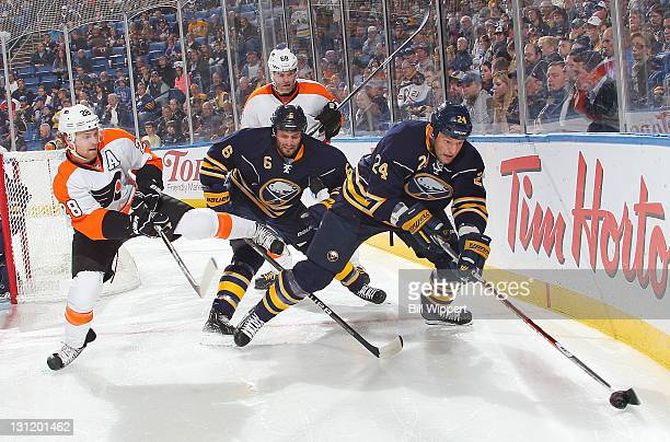 Mike Weber of the Buffalo Sabres defends Claude Giroux and Jaromir Jagr of the Philadelphia Flyers as teammate Robyn Regehr controls the puck behind...
