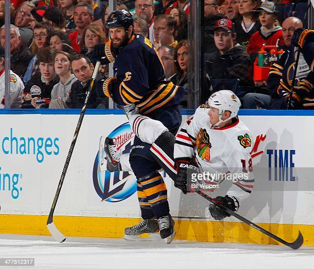 Mike Weber of the Buffalo Sabres upends Peter Regin of the Chicago Blackhawks on March 9, 2014 at the First Niagara Center in Buffalo, New York.