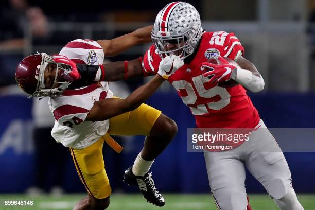 Mike Weber of the Ohio State Buckeyes carries the ball against Isaiah Langley of the USC Trojans in the first half during the Goodyear Cotton Bowl...
