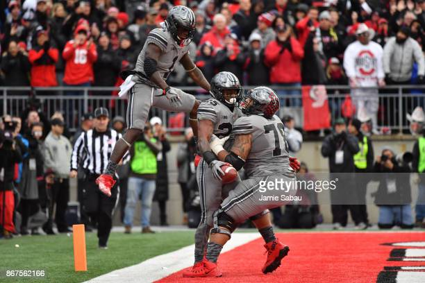 Mike Weber of the Ohio State Buckeyes celebrates in the end zone with Johnnie Dixon and Demetrius Knox after scoring on a twoyard touchdown run in...