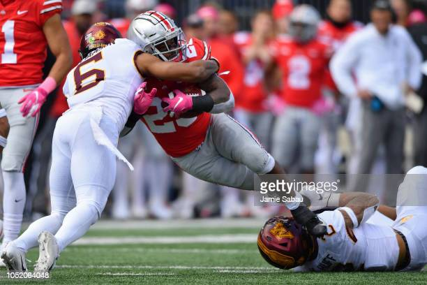 Mike Weber of the Ohio State Buckeyes is brought down by Chris Williamson of the Minnesota Golden Gophers and Julian Huff of the Minnesota Golden...