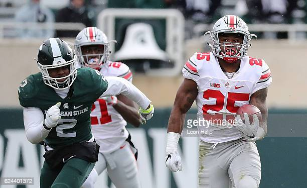 Mike Weber of the Ohio State Buckeyes runs for a long run as Montae Nicholson of the Michigan State Spartans makes the stop during the third quarter...