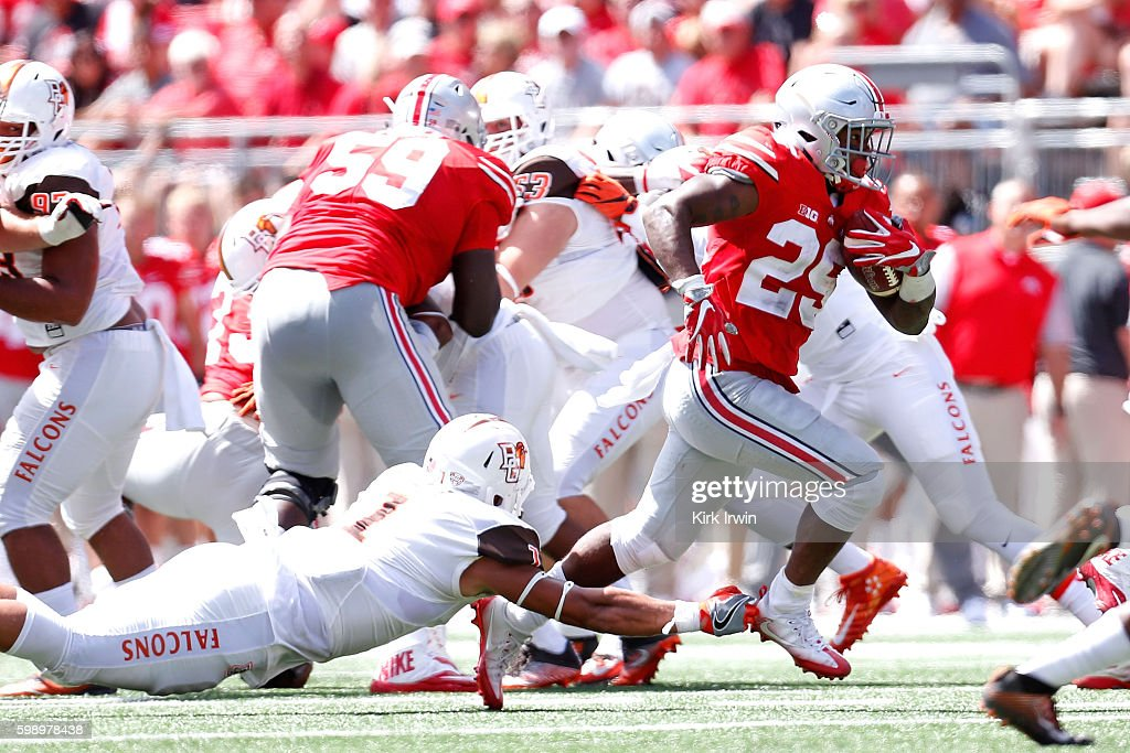 Mike Weber #25 of the Ohio State Buckeyes slips past an attempted tackle by Austin Valdez #1 of the Bowling Green Falcons during the second quarter on September 3, 2016 at Ohio Stadium in Columbus, Ohio.