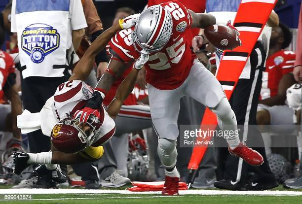 Mike Weber of the Ohio State Buckeyes stiff arms Isaiah Langley of the USC Trojans in the first half of the 82nd Goodyear Cotton Bowl Classic between...