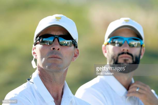 Mike Weir of Canada and Captains Assistant of the International Team and Adam Hadwin look on during the Thursday foursomes matches of the first round...