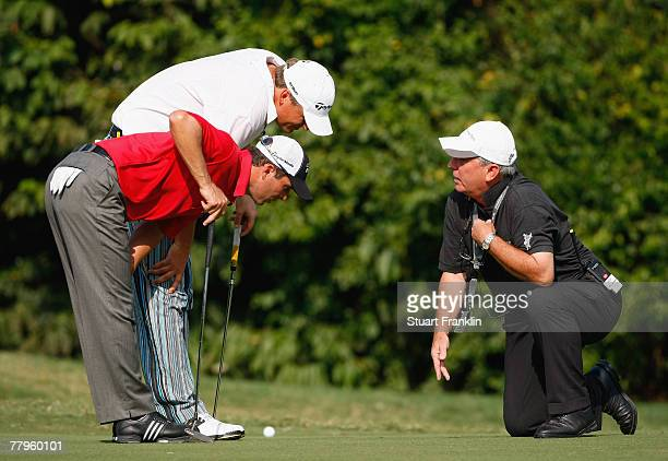 Mike Weir of Canada and playing partner Jarmo Sandelin of Sweden inspect the 12th hole with a referee after his ball jumped out of the cup and thus...