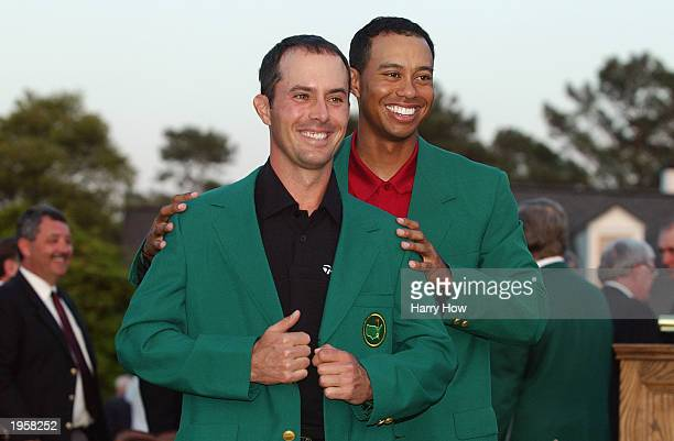 Mike Weir of Canada is presented with the green jacket by Tiger Woods of the USA after winning the play off after the final round of the 2003 Masters...