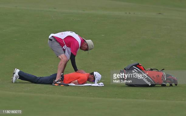 Mike Weir of Canada is stretched by his caddie on the 12th hole during the third round of the LECOM Suncoast Classic at Lakewood National Golf Club...