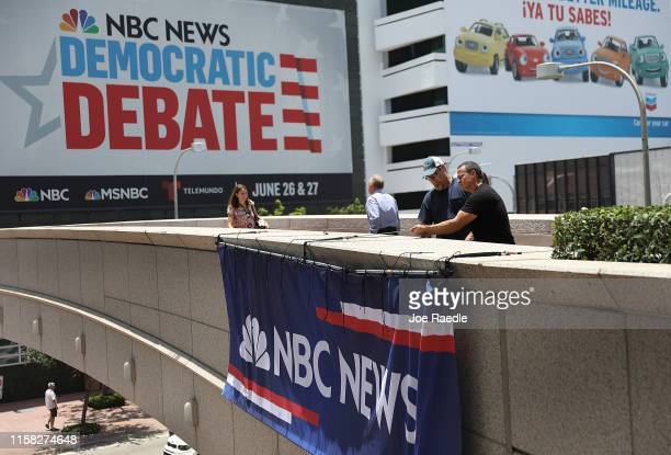 Mike Wetherill and Juan Suri place an NBC News banner at the Adrienne Arsht Center for the Performing Arts where the first Democratic presidential...