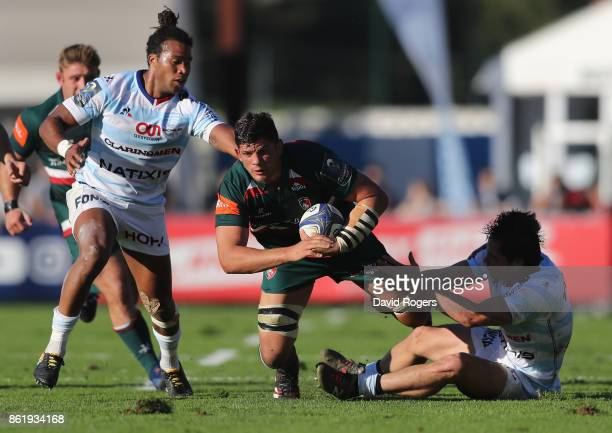 Mike Williams of Leicester is tackled by Teddy Thomas and Henry Chavancy during the European Rugby Champions Cup match between Racing 92 and...