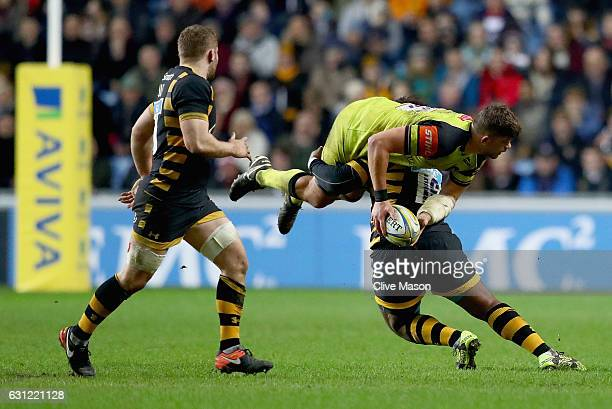 Mike Williams of Leicester Tigers is tackled by Ashley Johnson of Wasps during the Aviva Premiership match between Wasps and Leicester Tigers at The...