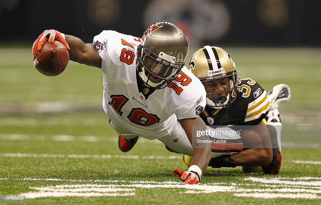 Mike Williams #19 of the Tampa Bay Buccaneers dives with the ball as he is tackled by Jabari Greer #33 of the New Orleans Saints during their game at Mercedes-Benz Superdome on November 6, 2011 in New Orleans, Louisiana.