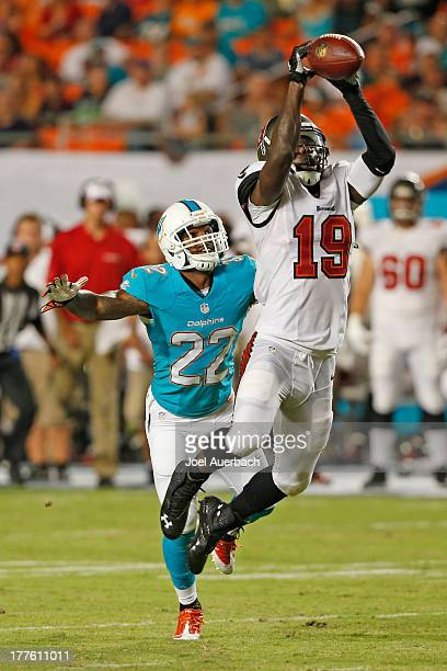 Mike Williams of the Tampa Bay Buccaneers is unable to hold onto the ball while being defended by Jamar Taylor of the Miami Dolphins during a...