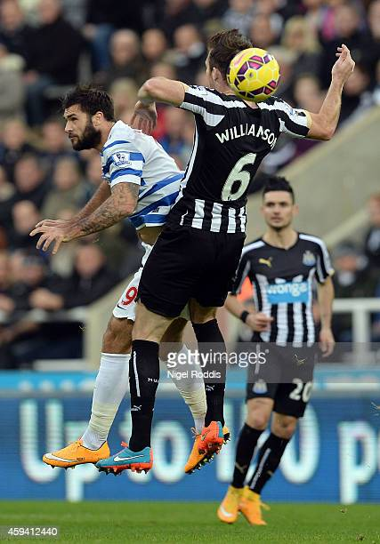 Mike Williamson of Newcastle United challenges Charlie Austin of Queeens Park Rangers during the Barclays Premier League football match between...