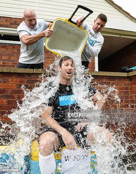 Mike Williamson undertakes the 'Ice Bucket Challenge' with Masseurs Wayne Farrage and Mick Holland standing above pouring the ice cold water after a...