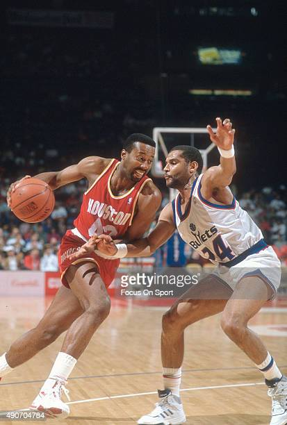 Mike Woodson of the Houston Rockets drives on Jeff Malone of the Washington Bullets during an NBA basketball game circa 1990 at the Capital Centre in...