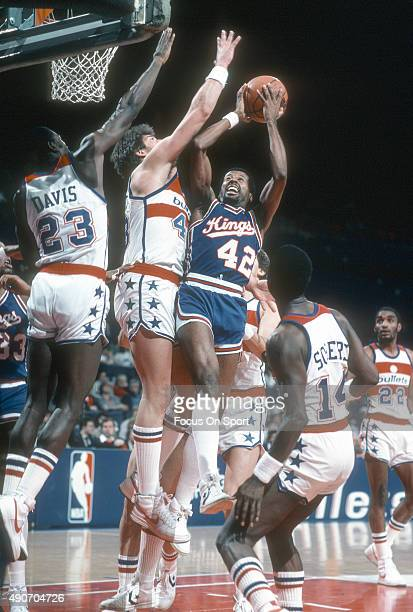 Mike Woodson of the Kansas City Kings looks to get his shot off over Jeff Ruland and Charles Davis of the Washington Bullets during an NBA basketball...