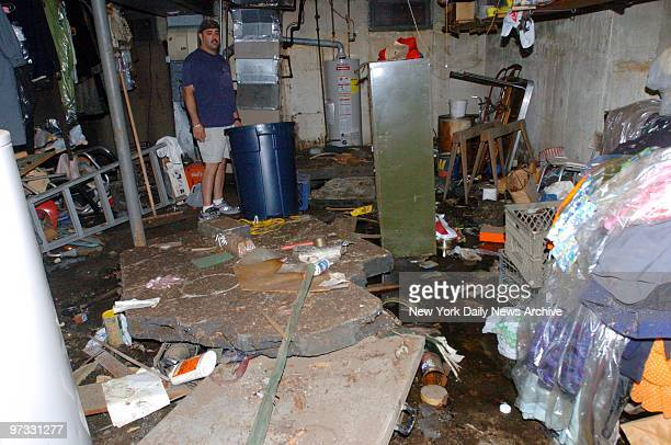 Mike Wray surveys damage caused by flooding in the basement of a house on 160th St in Whitestone Queens during a storm on Aug 11 In a neighboring...