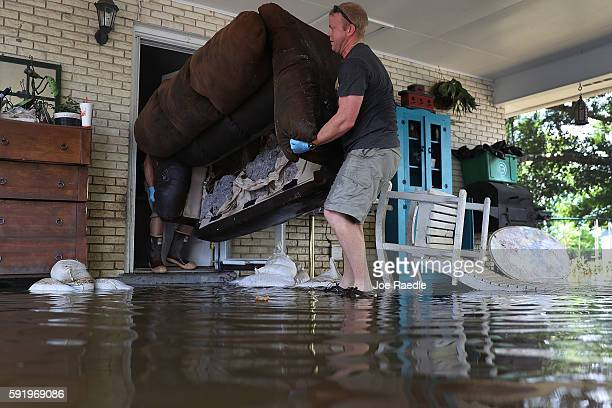 Mike Wroten and Matt Wroten throw a water logged couch out of the house as they clear Mike's home out after flood waters inundated it on August 19...