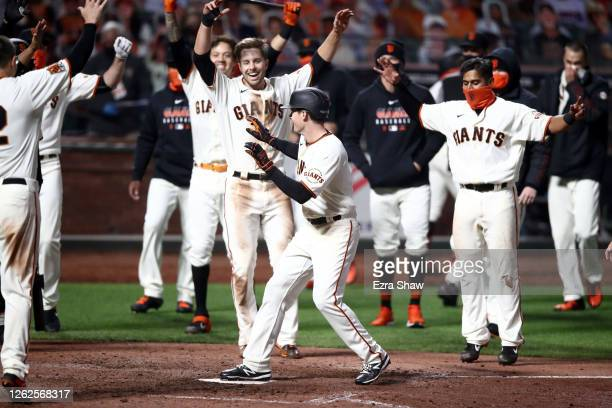 Mike Yastrzemski of the San Francisco Giants celebrates with teammates after he hit a walk-off home run in the ninth inning against the San Diego...