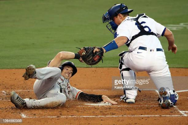 Mike Yastrzemski of the San Francisco Giants slides into home base against Will Smith of the Los Angeles Dodgers during the third inning at Dodger...