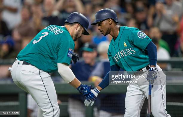 Mike Zunino of the Seattle Mariners is congratulated by Jarrod Dyson of the Seattle Mariners after hitting a solo home run off of starting pitcher...